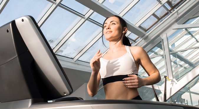 woman running on treadmilll in glass roof building
